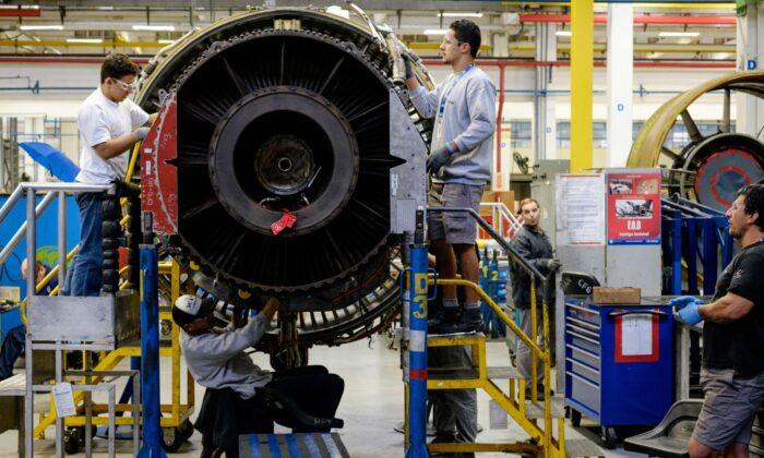Técnicos trabajando en un motor a reacción en una instalación de revisión de motores de aviación de General Electric (GE) en Petropolis, Río de Janeiro, Brasil, el 8 de junio de 2016. (YASUYOSHI CHIBA/AFP/Getty Images)
