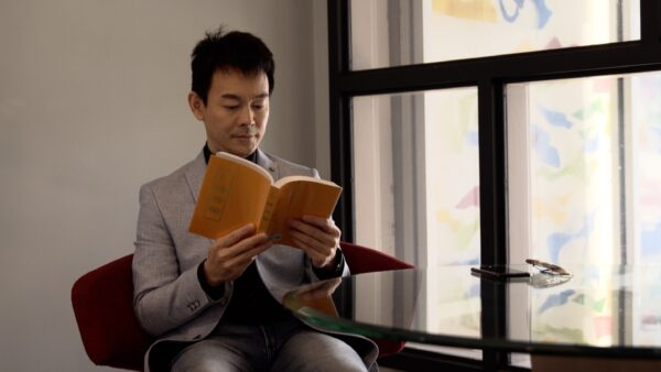 Ryan Jiang leyendo Zhuan Falun, el libro principal de Falun Dafa. (NTD Televisión)