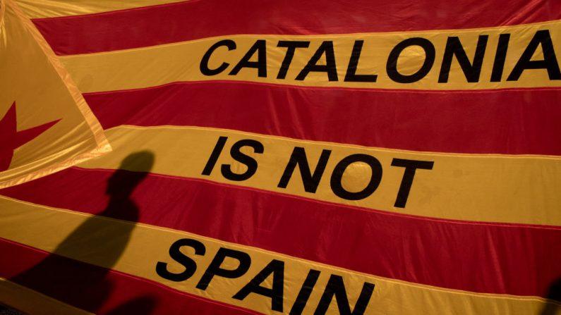 Sombras de manifestantes são vistas em uma bandeira catalã, enquanto milhares de cidadãos se reúnem na Plaza Universitat durante uma greve geral regional para protestar contra a violência que marcou o voto do referendo de domingo em 3 de outubro de 2017 em Barcelona, Espanha (Foto por Chris McGrath / Getty Images)