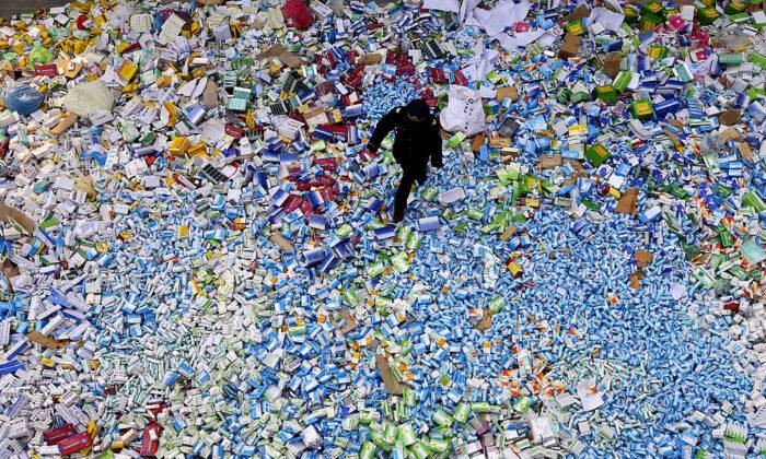 Un policía chino camina sobre un montón de medicamentos falsos incautados en Beijing en los últimos meses, el 14 de marzo de 2013. (STR/AFP vía Getty Images)