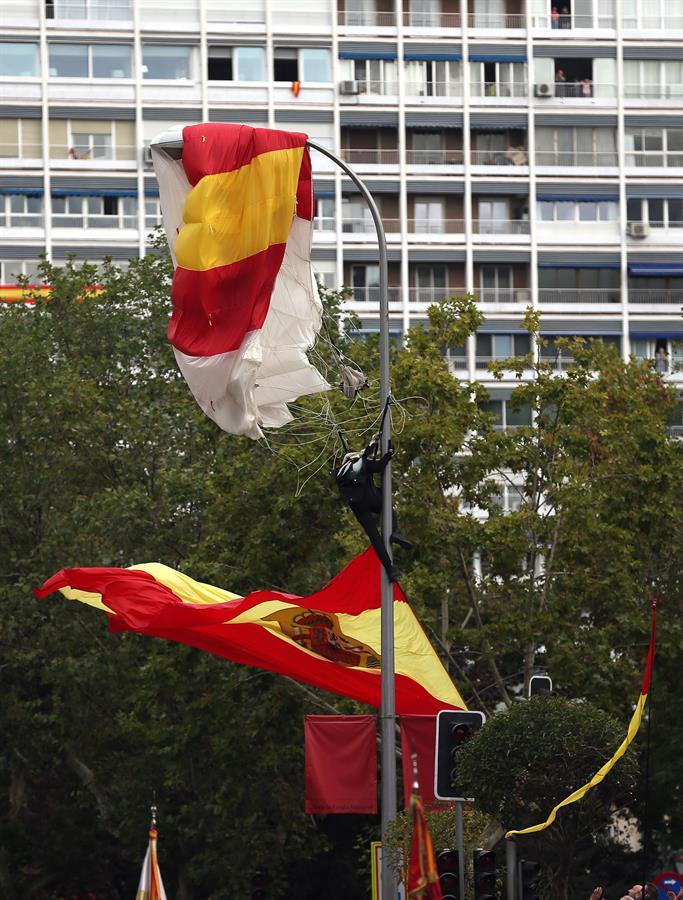 El miembro de la Brigada Paracaidista que descendía portando la bandera de España, en la farola en la que se enganchó momentos antes de tomar tierra en el madrileño Paseo de la Castellana, lugar en el que se celebra el desfile de la Fiesta Nacional, esta mañana en Madrid. EFE/Javier Lizón