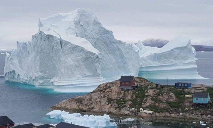 Um iceberg atrás de casas e edifícios nos arredores da vila de Innarsuit, um assentamento insular no município de Avannaata, no noroeste da Groenlândia (Magnus Kristensen / AFP / Getty Images)