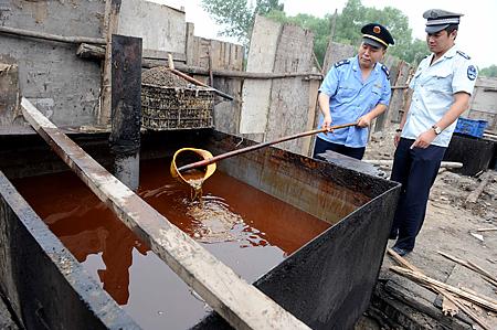 La policía inspecciona un aceite de cocina ilegal incautado durante una requisa en Beijing, el 2 de agosto de 2010. (STR/AFP/Getty Images)
