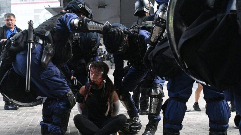 La policía de Hong Kong detiene a una mujer (en el suelo) cerca de las oficinas del gobierno central después de que miles participaron en una marcha no autorizada a través de Hong Kong el 29 de septiembre de 2019. (Mohd Rasfan/AFP a través de Getty Images)