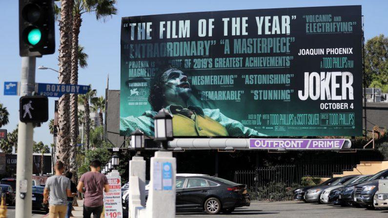 As pessoas passam por um cartaz exibido para o novo filme 'Coringa' em 3 de outubro de 2019 em West Hollywood, Califórnia. As medidas de segurança foram reforçadas em algumas cidades no fim de semana de estréia do filme, após preocupações com possíveis violências nos cinemas (Foto de Mario Tama / Getty Images)