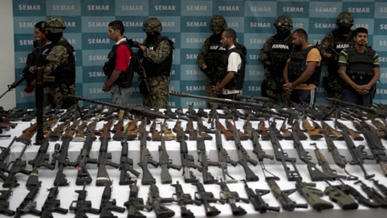Infantes de marina mexicanos escoltan a cinco presuntos narcotraficantes del cártel de Zetas frente a granadas, armas de fuego, cocaína y uniformes militares incautados en la Ciudad de México el 9 de junio de 2011. (Yuri Cortez/AFP/Getty Images)