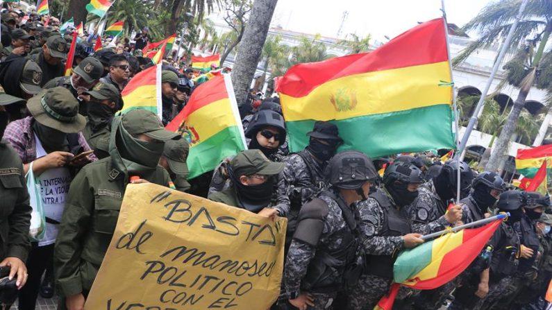 Un grupo de policías ondea la bandera tricolor de Bolivia mientras se repliega a una comisaría este sábado en la ciudad de Santa Cruz (Bolivia)(EFE/Juan Carlos Torrejón)