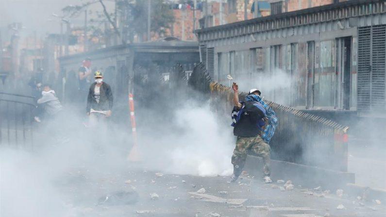 Manifestantes encapuchados enfrentan a miembros de la policía antidisturbios este viernes, en un sector de Patio Bonito, sur de Bogotá (Colombia). EFE/ Mauricio Dueñas Castañeda