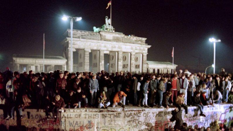 Miles de jóvenes berlineses orientales se aglomeran sobre el Muro de Berlín, cerca de la Puerta de Brandenburgo, en Alemania, el 11 de noviembre de 1989. El muro se derrumbó el 9 de noviembre (Gerard Malie/AFP/Getty Images)