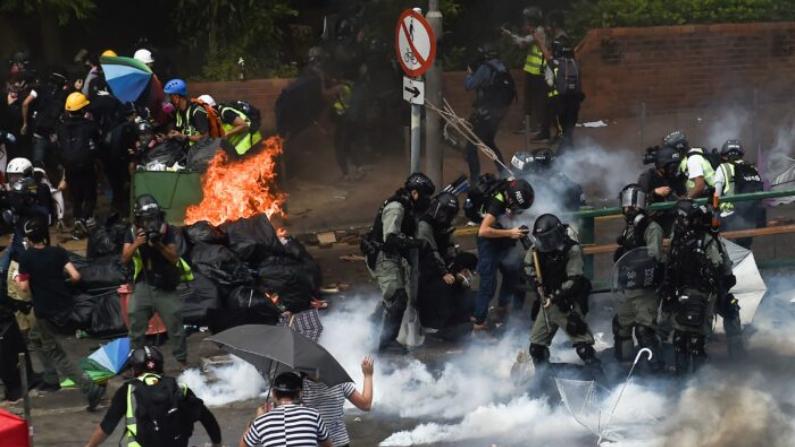 La policía antidisturbios hace arrestos cuando los manifestantes (Izq.) intentan encontrar un paso seguro fuera del campus de la Universidad Politécnica de Hong Kong en el distrito Hung Hom de Hong Kong el 18 de noviembre de 2019. (Ye Aung Thu/AFP vía Getty Images)