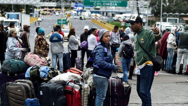 Migrantes venezolanos esperan afuera de la oficina de migraciones colombiana en el Puente Internacional Rumichaca, en la frontera entre Ipiales, Colombia y Tulcan, Ecuador, el 20 de agosto de 2018. (Luis Robayo / AFP / Getty Images)