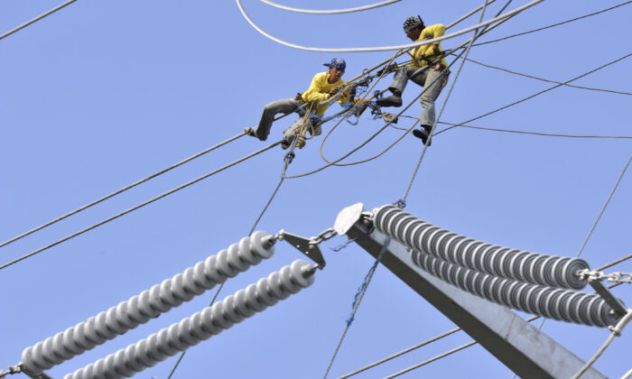Técnicos instalan cables en la línea de transmisión de energía de Transco en la ciudad de Santa Rosa, al sur de Manila, cuando el consorcio encabezado por chinos se hizo cargo oficialmente de una concesión de 25 años de la red eléctrica nacional de Filipinas como parte del programa de privatización del gobierno, el 15 de enero de 2009. (Romeo Gacad/AFP vía Getty Images)