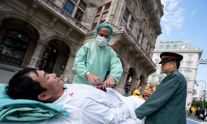 Practicantes de Falun Gong recrean la recolección forzada de órganos de prisioneros de conciencia por el régimen chino en una protesta en Viena, Austria, el 1 de octubre de 2018. (Joe Klamar/AFP vía Getty Images)