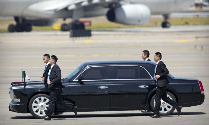 El personal de seguridad chino corre junto a la limusina que transporta al primer ministro italiano Giuseppe Conte cuando llega al Aeropuerto Internacional de la Capital de Beijing para asistir al Foro de la Franja y la Ruta en Beijing, el 26 de abril de 2019. (MARQUE SCHIEFELBEIN/AFP a través de Getty Images)