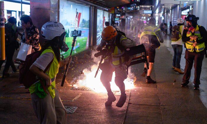 La reacción de los periodistas mientras la policía dispara gas lacrimógeno desde la estación del Metro de Causeway Bay durante unos enfrentamientos con manifestantes pro-democracia en Hong Kong, el 8 de septiembre de 2019. (Philip Fong/AFP/Getty Images)