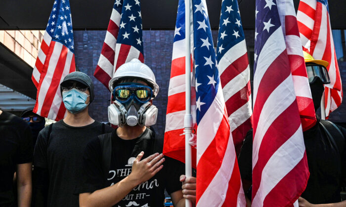 Los estudiantes sostienen la bandera de los Estados Unidos y cantan el Star-Spangled Banner en la Universidad de Hong Kong (HKU) en Hong Kong el 20 de septiembre de 2019, mientras se reúnen para que el Congreso de los Estados Unidos apruebe la Ley de Derechos Humanos y Democracia de Hong Kong. (Foto de Anthony WALLACE / AFP) (El crédito de la foto debe leer ANTHONY WALLACE / AFP a través de Getty Images)