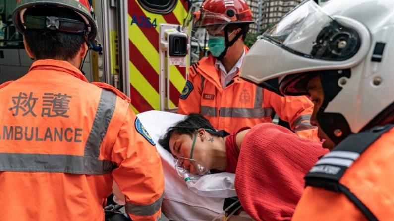 Un peatón es elevado a una ambulancia después de inhalar gas lacrimógeno en el distrito de Wan Chai en Hong Kong el 6 de octubre de 2019. (Anthony Kwan/Getty Images)
