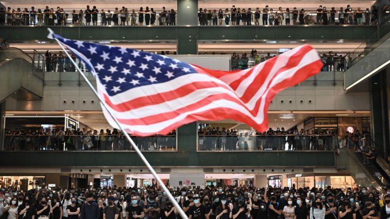 La gente ondea la bandera de Estados Unidos durante un mitin de flash mob dentro de un centro comercial en el distrito de Sha Tin en Hong Kong el 13 de octubre de 2019. (Philip Fong/AFP a través de Getty Images)