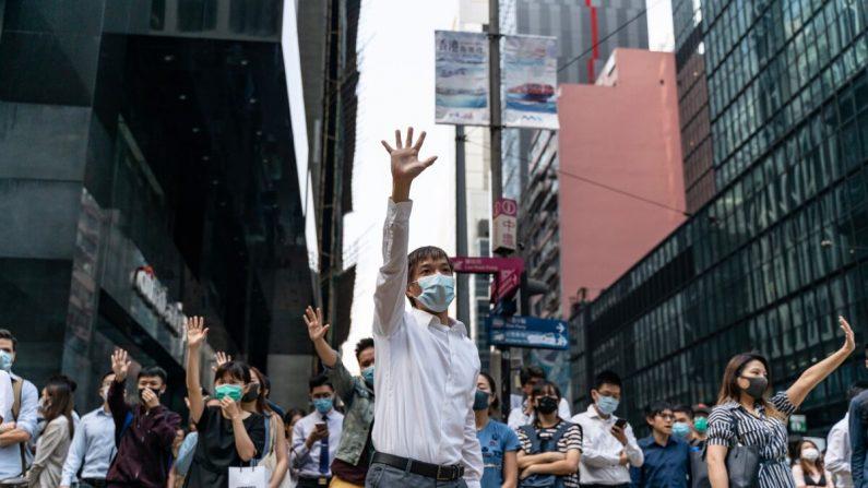 Partidarios pro-democracia hacen gestos al ocupar una calle en el distrito central de Hong Kong, el 14 de noviembre de 2019. (Anthony Kwan/Getty Images)