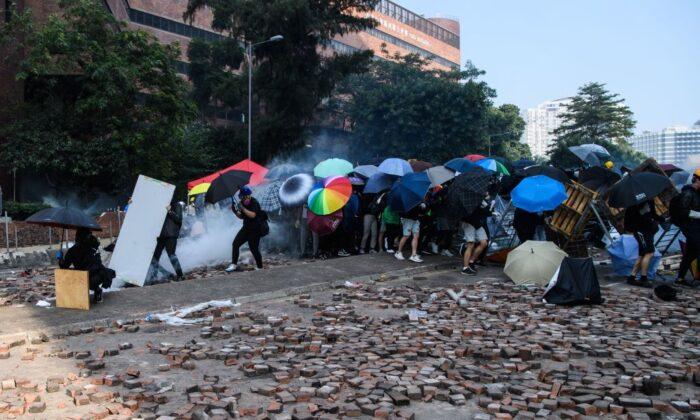 Manifestantes intentan escapar del campus de la Universidad Politécnica de Hong Kong después de que fuera rodeada por la policía en el distrito Hung Hom de Hong Kong el 18 de noviembre de 2019. (Anthony Wallace/AFP vía Getty Images)