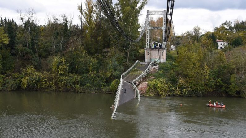 Los equipos de rescate navegan cerca de un puente colgante que se derrumbó el 18 de noviembre de 2019 en Mirepoix-sur-Tarn, cerca de Toulouse, en el suroeste de Francia. (Eric Cabanis / AFP / Getty Images)