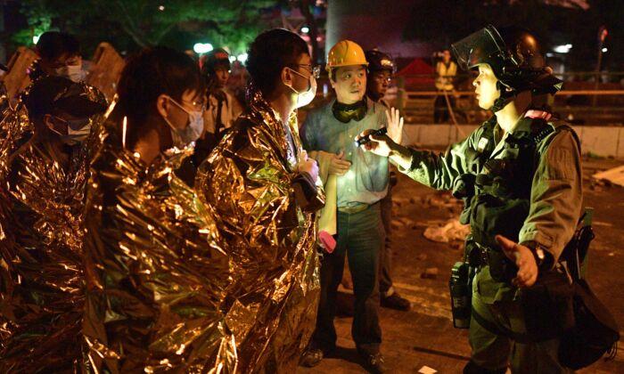 Un policía inspecciona a los manifestantes enfermos y heridos envueltos en mantas térmicas de emergencia, mientras se preparan para abandonar el campus de la Universidad Politécnica de Hong Kong en el Hung Hom de Hong Kong el 19 de noviembre de 2019. (NICOLAS ASFOURI/AFP vía Getty Images)