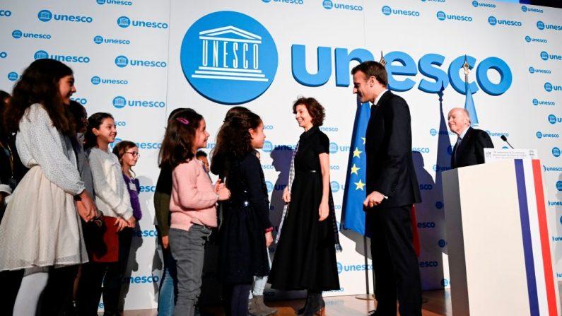La Directora General de la UNESCO, Audrey Azoulay, el Presidente francés Emmanuel Macron y el Ombudsman francés Jacques Toubon reciben a los niños durante el 30 aniversario de la Convención sobre los Derechos del Niño (UNCRC) en la UNESCO, en París, el 20 de noviembre de 2019. (ERIC FEFERBERG/POOL/AFP via Getty Images)