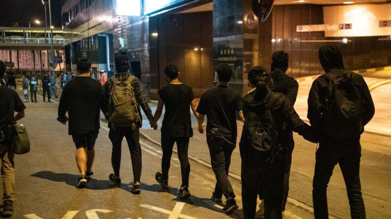 Manifestantes se toman de la mano mientras dejan la Universidad Politécnica de Hong Kong para entregarse a la policía, el 22 de noviembre de 2019. (Laurel Chor/Getty Images)