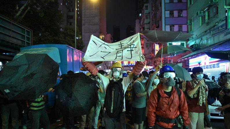 Los manifestantes se reúnen mientras los policías intentan despejar una calle después que la policía retirara una barricada bajo una orden judicial en un sitio de protesta a favor de la democracia en el distrito de Mongkok de Hong Kong. (Créditos PHILIPPE LOPEZ/AFP vía Getty Images)