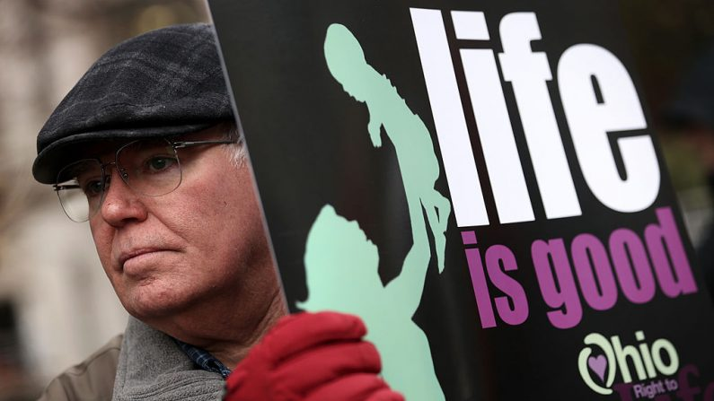 El activista contra el aborto Brian Normile de Beavercreek, Ohio, sostiene un cartel durante una vigilia de oración frente a Planned Parenthood el 21 de enero de 2014 en Washington, DC. (Alex Wong/Getty Images)