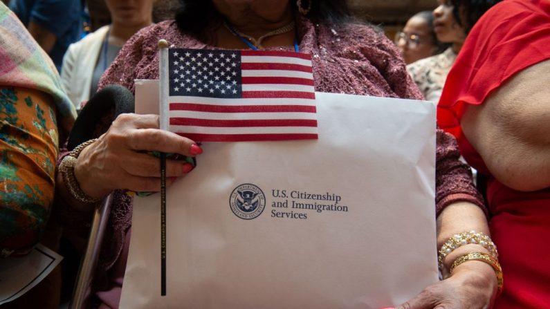 Una mujer sostiene la bandera y sus documentos mientras el Servicio de Ciudadanía e Inmigración de los Estados Unidos da la bienvenida a 200 nuevos ciudadanos de 50 países durante una ceremonia en honor del Día de la Independencia en la Biblioteca Pública de Nueva York el 3 de julio de 2018 en Nueva York. (Bryan R. Smith/AFP/Getty Images)