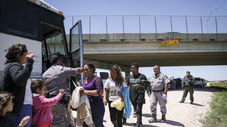 Un gran grupo de extranjeros ilegales sube a un autobús con destino a las instalaciones de procesamiento de la Patrulla Fronteriza, después de haber sido detenidos por la Patrulla Fronteriza cerca de McAllen, Texas, el 18 de abril de 2019. (Charlotte Cuthbertson/La Gran Época)