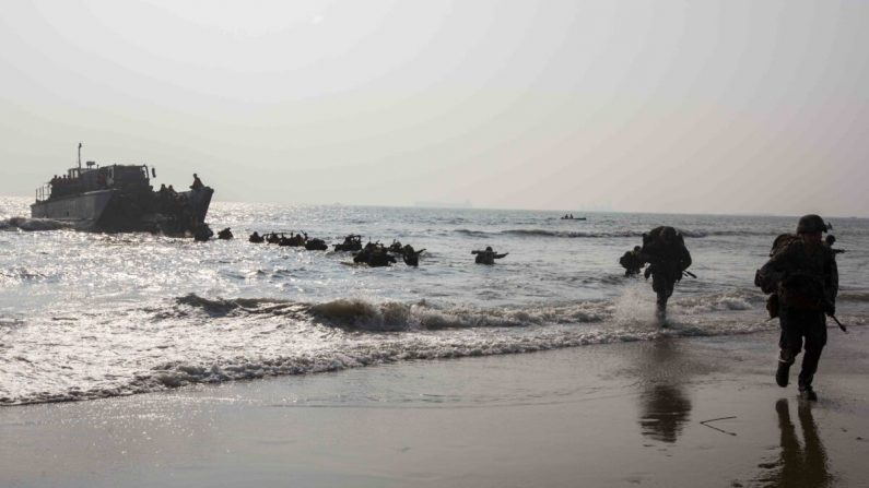 Los infantes de marina estadounidenses actualmente bajo el 4to Regimiento de Infantería de Marina, la 3ra División de Infantería de Marina, y miembros del ejército indio corren a la costa en la playa de Kakinada, India, el 19 de noviembre de 2019. (Cuerpo de Infantería de Marina de los EE.UU. por Lance Cpl. Christian Ayers)
