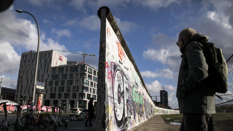 Los turistas se paran en una antigua sección del Muro de Berlín llamada la Galería East Side, en el primer día de los eventos para celebrar el 30 aniversario de la caída del Muro de Berlín, el 4 de noviembre de 2019 en Berlín, Alemania. (Carsten Koall/Getty Images)