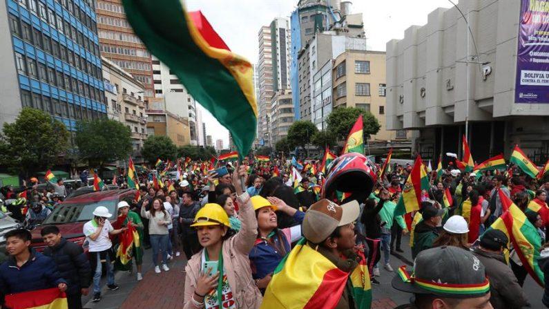 Cidadãos e policiais bolivianos comemoram a renúncia do presidente da Bolívia, Evo Morales, neste domingo em La Paz (Bolívia) (EFE / Martin Alipaz)