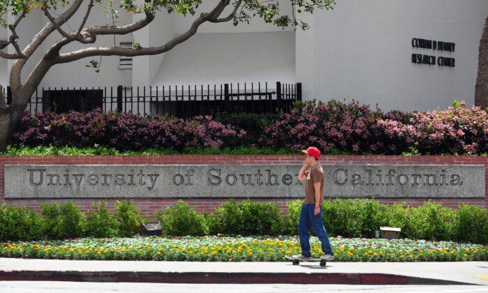 Un estudiante monta su monopatín pasando por una entrada al campus de la Universidad del Sur de California (USC) en Los Ángeles, EE.UU., el 11 de abril de 2012. (Frederic J. Brown/AFP vía Getty Images)