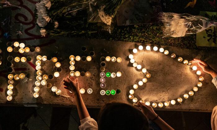 La gente enciende velas durante una oración en memoria del estudiante universitario Alex Chow en Hong Kong, el 9 de noviembre de 2019. (Anthony Kwan/Getty Images)