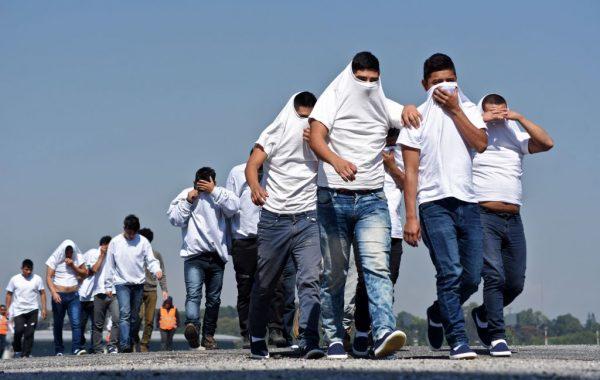 Imigrantes guatemaltecos deportados dos Estados Unidos cobrem o rosto ao chegar à Base Aérea da Cidade da Guatemala em 21 de novembro de 2019 (ORLANDO ESTRADA / AFP via Getty Images)