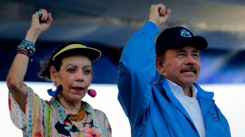 El líder del régimen nicaragüense Daniel Ortega y su esposa, Rosario Murillo, levantan los puños durante la celebración del 51 aniversario de la campaña de la guerrilla pancasana en Managua el 29 de agosto de 2018 (Inti Ocon/AFP vía Getty Images)