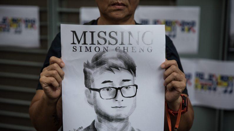 Mulher segura cartaz mostrando retrato de funcionário do consulado britânico Simon Cheng, do lado de fora do consulado em 21 de agosto de 2019 em Hong Kong (Chris McGrath / Getty Images)
