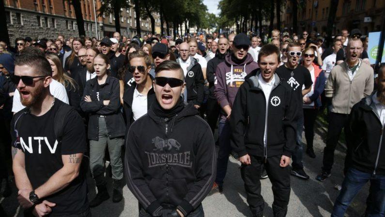 Apoiadores do Movimento de Resistência Nórdica, uma organização classificada como neonazi, durante uma manifestação na praça Kungsholmstorg em Estocolmo, Suécia, em 25 de agosto de 2018. - A manifestação e sua contra-demonstração foram separadas por uma presença policial maciça (Foto por FREDRIK PERSSON / AFP via Getty Images)