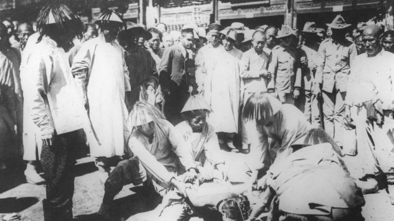 A multidão se reúne para assistir as pessoas segurando uma vítima que é torturada e executada durante a Revolução na China em 1912 (Foto de Hulton Archive / Getty Images)