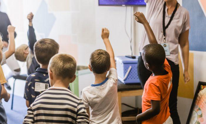 Niños y niñas que levantan la mano en un salón de clases. (Nicole Honeywill/Unsplash)