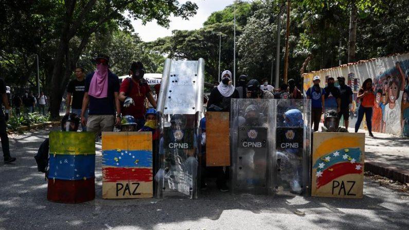 Manifestantes se escondem atrás de escudos enquanto colidem com membros da Polícia Nacional Bolivariana (PNB), durante um protesto estudantil, nas entradas da Universidade Central da Venezuela, em Caracas, Venezuela, 14 de novembro de 2019 (EPA / RAYNER PENA R.)