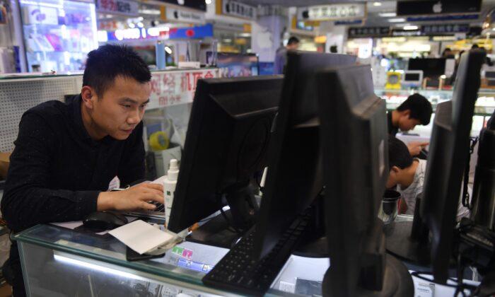 Un hombre repara un ordenador portátil en un centro comercial de Beijing, el 30 de marzo de 2018. (GREG BAKER/AFP vía Getty Images)