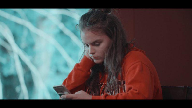 """Claire mirando su teléfono en """"Like"""" (2019), una película documental sobre las redes sociales. (IndieFlix)"""