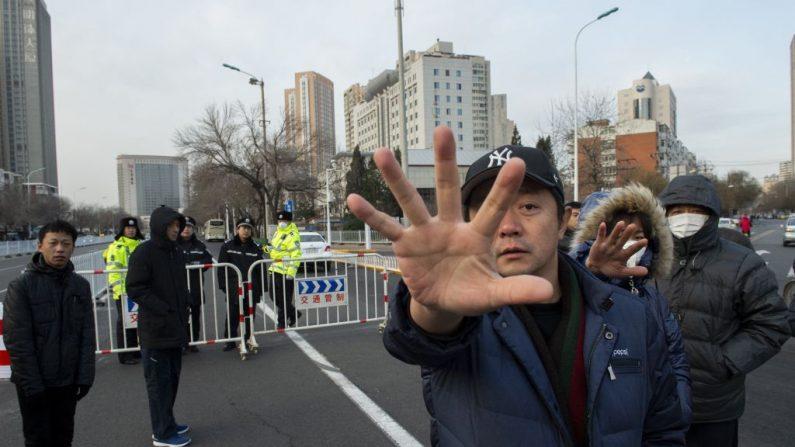 Policías vestidos de civil indican que no se permite fotografiar. Foto tomada el 26 de diciembre de 2018 en Tianjin (China). (NICOLAS ASFOURI / AFP a través de Getty Images)
