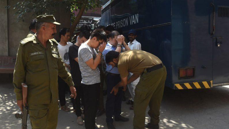 Policías pakistaníes escoltan a chinos esposados acusados de atraer a jóvenes pakistaníes a falsos matrimonios y obligarlas a prostituirse en China, cuando llegan a los tribunales de Lahore el 10 de junio de 2019. - (Foto de ARIF ALI / AFP) (Crédito foto: ARIF ALI/AFP vía Getty Images)