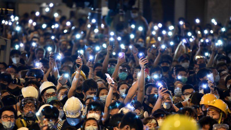 Los manifestantes sostienen sus teléfonos móviles mientras se reúnen frente a la sede de la policía en Hong Kong el 21 de junio de 2019. (HECTOR RETAMAL/AFP a través de Getty Images)