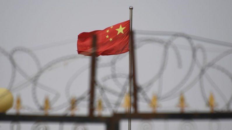 Esta foto tirada em 4 de junho de 2019 mostra a bandeira chinesa atrás do arame farpado em um complexo habitacional em Yangisar, sul de Kashgar, na região oeste de Xinjiang, China (GREG BAKER / AFP via Getty Images)